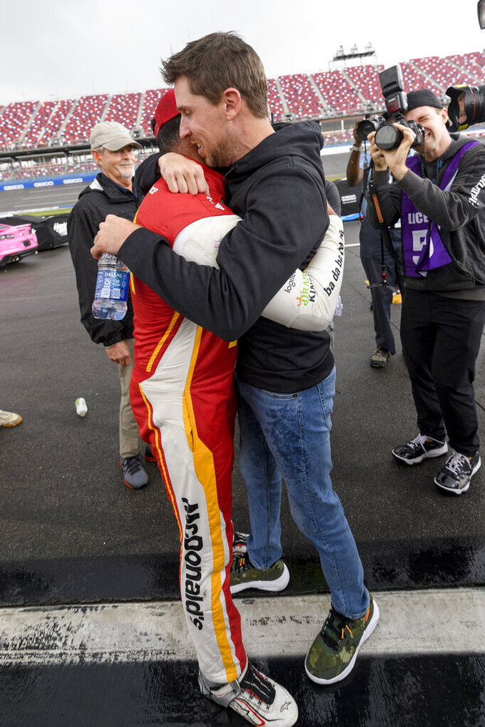 Bubba Wallace, front left, is congratulated by Denny Hamlin, front right, after Wallace was pronounced the winner while on pit row during a rain delay in a NASCAR Cup series auto race Monday, Oct. 4, 2021, in Talladega, Ala. (AP Photo/John Amis)