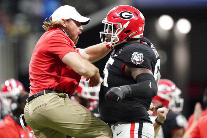 Georgia defensive lineman Devonte Wyatt (95) celebrates a hit on Cincinnati quarterback Desmond Ridder (9) during the second half of the Peach Bowl NCAA college football game, Friday, Jan. 1, 2021, in Atlanta. (AP Photo/Brynn Anderson)