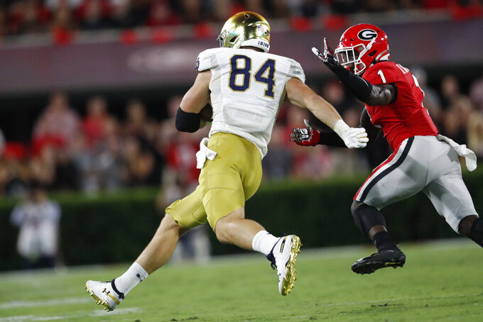 Notre Dame tight end Cole Kmet (84) runs against Georgia defensive back Divaad Wilson (1) during the first half of an NCAA college football game, Saturday, Sept. 21, 2019, in Athens, Ga. (AP Photo/John Bazemore)