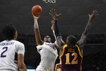 Connecticut's Josh Carlton, center, goes up for a basket as Iona's Tajuan Agee, right, defends, in the first half of an NCAA college basketball game, Wednesday, Dec. 4, 2019, in Storrs, Conn. (AP Photo/Jessica Hill)