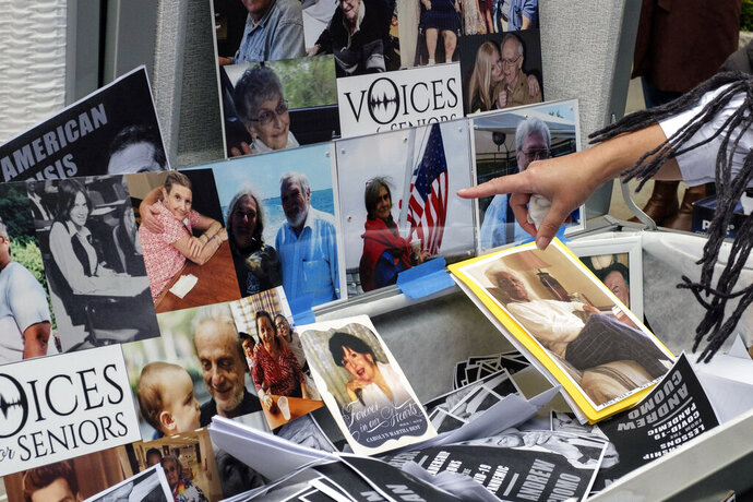 FILE - In this Oct. 18, 2020, file photo, families of COVID-19 victims who died in New York nursing homes gather in front of Cobble Hill Heath Center in the Brooklyn borough of New York, to demand New York Gov. Andrew Cuomo apologize for his response to clusters in nursing homes during the pandemic. The Justice Department vastly expanded its inquiry into whether New York is undercounting the number of nursing home residents dead from the coronavirus, demanding the state turn over death tallies from hundreds of private facilities. (AP Photo/Yuki Iwamura, File)