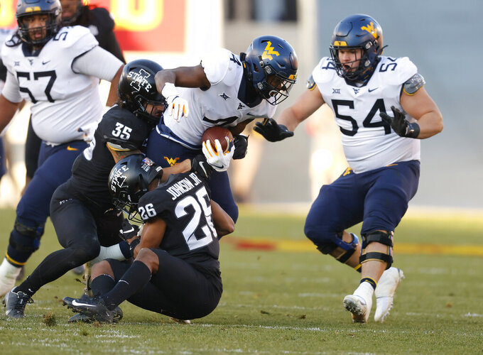 West Virginia running back Leddie Brown, center, runs the ball as he is brought down by Iowa State linebacker Jake Hummel, left, and defensive back Anthony Johnson, bottom, during the first half of an NCAA college football game, Saturday, Dec. 5, 2020, in Ames, Iowa. (AP Photo/Matthew Putney)