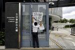 A security guard removes a poster which left by protesters outside the Legislative Council in Hong Kong, Tuesday, June 18, 2019. Hong Kong's government headquarters reopened Tuesday as the number of protesters outside dwindled to a few dozen and life returned to normal in the former British colony. (AP Photo/Vincent Yu)