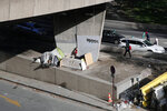A migrant has his tent under the rink highway in Paris, France, Wednesday, Nov. 6, 2019. French Prime Minister Edouard Philippe has said France needs to