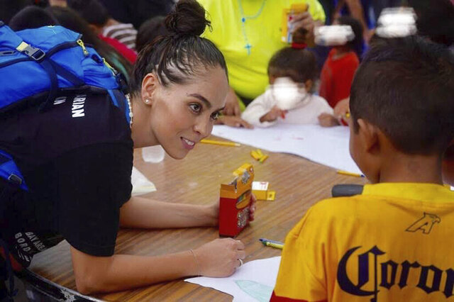 In this October 2019 photo provided by Pocho Sanchez, Daniela Dominguez, assistant professor in counseling psychology at University of San Francisco, draws and chats with children from Honduras at a migrant camp in Matamoros, Mexico. Dominguez said mutual aid networks are part of the Latino culture where people may feel safer getting help from their own community rather than government entities or formal charities. (Pocho Sanchez via AP)