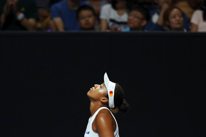 Naomi Osaka of Japan reacts as she plays against Petra Kvitova of the Czech Republic during their WTA Finals Tennis Tournament in Shenzhen, China's Guangdong province, Sunday, Oct. 27, 2019. (AP Photo/Andy Wong)