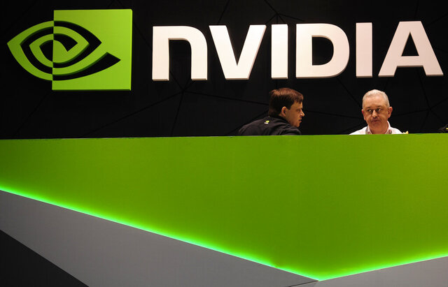 FILE - In this file photo dated Thursday, Feb. 27, 2014, people gather in the Nvidia booth at the Mobile World Congress mobile phone trade show in Barcelona, Spain.  U.K regulators said Wednesday Jan. 6, 2021, they are investigating graphics computer chip maker Nvidia's $40 billion purchase of chip designer Arm Holdings over concerns about its effect on competition.  (AP Photo/Manu Fernandez, FILE)