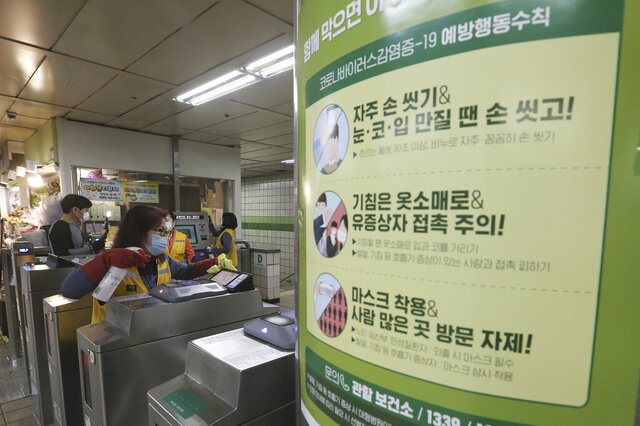 A worker disinfects ticket gates next to a poster about precautions against the new coronavirus at a subway station in Seoul, South Korea, Wednesday, April 29, 2020. The signs read