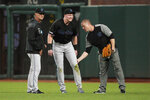 Miami Marlins right fielder Garrett Cooper, center, grimaces as a trainer checks on him and manager Don Mattingly, left, watches during the first inning against the San Francisco Giants in a baseball game Friday, Sept. 13, 2019, in San Francisco. Cooper was taken out of the game. (AP Photo/Tony Avelar)