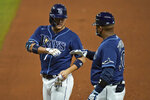 Tampa Bay Rays' Yoshi Tsutsugo, of Japan,, left, celebrates with first base coach Ozzie Timmons after his RBI single off Boston Red Sox relief pitcher Robinson Leyer during the seventh inning of a baseball game Friday, Sept. 11, 2020, in St. Petersburg, Fla. (AP Photo/Chris O'Meara)