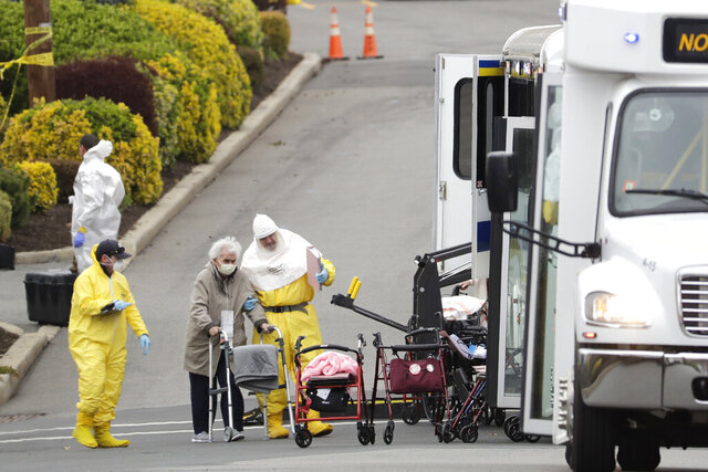 FILE- In this March 25, 2020 file photo, residents from St. Joseph's Senior Home are helped on to buses in Woodbridge, N.J. On Wednesday, Sept. 16, 2020, New Jersey Gov. Phil Murphy signed into law four bills aimed at improving nursing home care after the COVID-19 outbreak devastated long-term care center residents and, at times, overwhelmed facilities. (AP Photo/Seth Wenig)