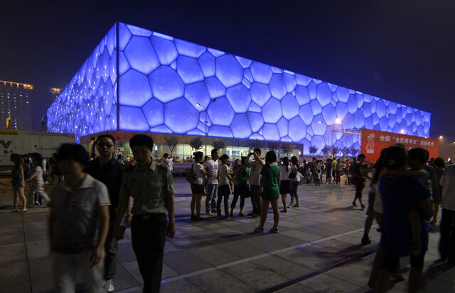 """File-Visitors walk past the National Aquatics Center, known as the Water Cube, on the eve of the one-year anniversary of the opening of the Olympic Games, in Beijing Friday, Aug. 7, 2009. The Olympics are remembered for the stars. That was true in Beijing in 2008, and the stars were Michael Phelps and Usain Bolt. But Beijing is also storied for its signature venues like the """"Bird's Nest"""" stadium, and the """"Water Cube"""" swimming venue. No Olympics before — or since — have impacted a city the way the Olympics did Beijing.  (AP Photo/Greg Baker, File)"""
