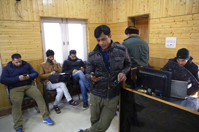 In this Jan. 30, 2020, photo, Kashmiri journalists browse the internet on their mobile phones inside the media center set up by government authorities in Srinagar, Indian controlled Kashmir. Six months after India stripped restive Kashmir of its semi-autonomy, enforcing a total communications blackout, it has restored limited internet at slow speeds with access only to government-approved websites. Since Modi came into power in 2014, the internet has been suspended more than 365 times in India, according to the global digital rights group Access Now. (AP Photo/ Dar Yasin)