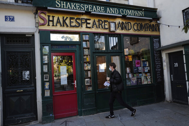 A man walks by the closed English and American literature Shakespeare and Co. bookstore in Paris, France, Thursday, Nov. 05, 2020. Iconic Parisian bookshop Shakespeare and Co. has launched a support appeal to its readers after its owners say that coronavirus-linked losses, and a crippling months-long lockdown, have left the future of the veritable institution in doubt.