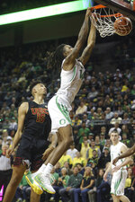 Oregon's C.J. Walker, right, dunks the ball past Southern California's Isaiah Mobley, left, during the first half of an NCAA basketball game in Eugene, Ore., Thursday, Jan. 23, 2020. (AP Photo/Chris Pietsch)
