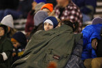 Bundled up against heavy, cold winds, fans cover up to watch the first half of an NCAA college football game between Utah State and Air Force Saturday, Oct. 26, 2019, at Air Force Academy, Colo. (AP Photo/David Zalubowski)