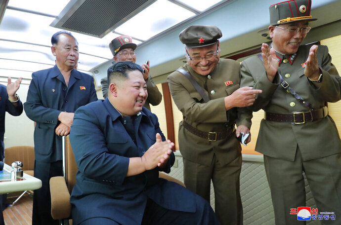 In this Friday, Aug. 16, 2019, photo provided Saturday, Aug. 17, by the North Korean government, North Korean leader Kim Jong Un, center, watches the test firing of an unspecified new weapon at an undisclosed location in North Korea. North Korea on Saturday said leader Kim supervised another test-firing of an unspecified new weapon that extended a streak of weapons demonstrations seen as an attempt to pressure Washington and Seoul over slow nuclear negotiations and their joint military exercises.  The content of this image is as provided and cannot be independently verified. Korean language watermark on image as provided by source reads: