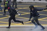 Riot police clash with  protesters calling for electoral reforms and a boycott of the Chinese Communist Party in Hong Kong, Sunday, Jan. 19, 2020. Hong Kong has been wracked by often violent anti-government protests since June, although they have diminished considerably in scale following a landslide win by opposition candidates in races for district councilors late last year. (AP Photo/Ng Han Guan)