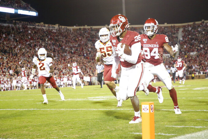 Oklahoma Sooners running back Kennedy Brooks (26) scores a touchdown during the NCAA football game between the against the Iowa State Cyclones and the Oklahoma Sooners at Gaylord Family-Oklahoma Memorial Stadium in Norman, Okla., on Saturday, Nov. 9, 2019. (Ian Maule/Tulsa World via AP)
