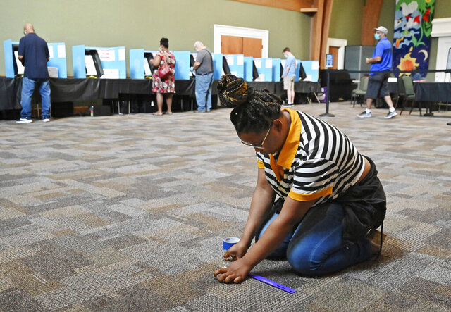 Kasharri Blacknell, a poll worker, places tape indicators for maintaining social distancing as Gwinnett County residents cast their votes during the Georgia primary elections at Pleasant Hill Presbyterian Church in Duluth, Ga., Tuesday, June 9, 2020. (Hyosub Shin/Atlanta Journal-Constitution via AP)