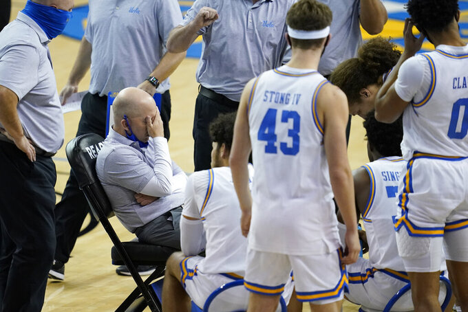 UCLA coach Mick Cronin covers his face with his hand during a timeout in the first half of the team's NCAA college basketball game against Arizona State on Saturday, Feb. 20, 2021, in Los Angeles. (AP Photo/Ashley Landis)