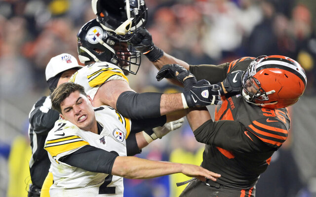 FILE - In this Nov. 14 2019, file photo, Cleveland Browns defensive end Myles Garrett (95) hits Pittsburgh Steelers quarterback Mason Rudolph (2) with a helmet during the second half of an NFL football game, in Cleveland. Garrett knows his ugly, helmet-swinging assault on Rudolph last season will always follow him. Speaking to reporters Thursday, July 16, 2020, for the first time since Nov. 14, Garrett, who was suspended six games by the NFL for his actions, touched on a wide range of topics during a 25-minute Zoom conference call. (AP Photo/David Richard, File)
