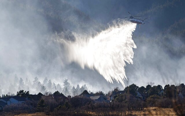 A Chinook helicopter drops water on a wildfire near Bear Creek Regional Park on the westside of Colorado Springs, Colo., Thursday, Nov. 19, 2020. About 235 homes were evacuated near the park as firefighters battled the fire on the ground and in the air. (Christian Murdock/The Gazette via AP)