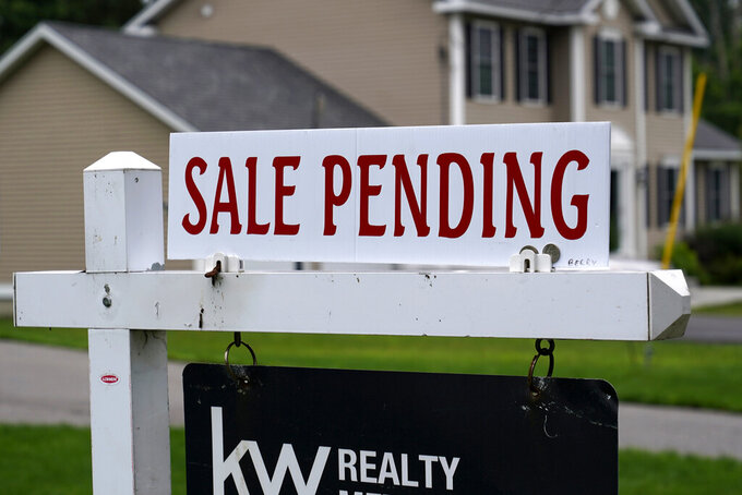 """A """"sale pending"""" sign is posted outside a single family home in a residential neighborhood, Wednesday, July 14, 2021, in Derry, N.H. Mortgage rates were mixed this week. The benchmark 30-year loan fell for the third straight week amid lingering concerns over the recent surge in inflation. Mortgage buyer Freddie Mac reports that the average for the 30-year home loan eased to 2.88% from 2.90% last week, down from its peak this year of 3.18% in April.  (AP Photo/Charles Krupa)"""