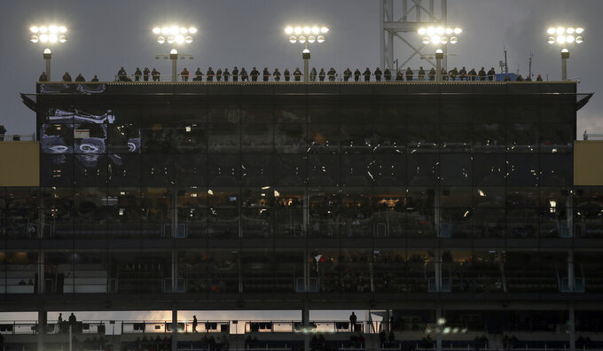 Spotters work from the roof of the press box during the NASCAR Cup Series auto race at Kansas Speedway in Kansas City, Kan., Saturday, May 11, 2019. (AP Photo/Orlin Wagner)