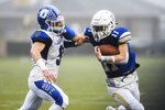Newtown's Mike Ricks (11) blocks Darien's Sam Wilson (9) as the Newtown Nighthawks take on the Darien Blue Wave Class LL state football championship at Trumbull High School, Saturday, Dec. 14, 2019, in Trumbull, Conn. Newtown won 13-7. Newtown marked the seventh anniversary of the massacre at Sandy Hook Elementary School with vigils, church services and a moment of joy when the community's high school football team, with a shooting victim's brother as linebacker, won the state championship Saturday in a last-minute thrill. (Kassi Jackson/Hartford Courant via AP)