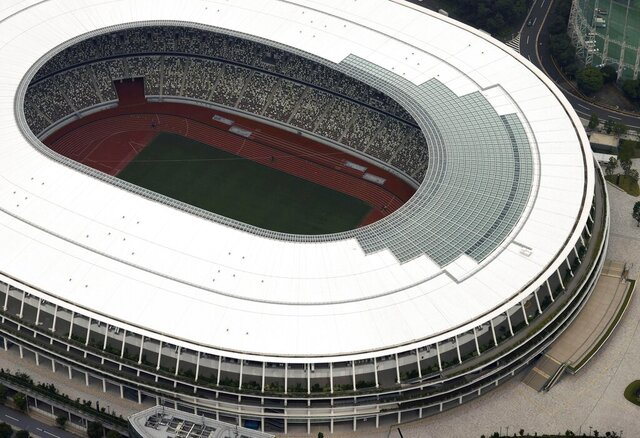 This aerial photo shows the New National Stadium, main stadium for the Tokyo Olympics and Paralympics, in Tokyo, Tuesday, July 21, 2020. The postponed Tokyo Olympics have again reached the one-year-to-go mark. But the celebration is small this time with more questions than answers about how the Olympics can happen in the middle of a pandemic. That was before COVID-19 postponed the Olympics and pushed back the opening to July 23, 2021. (Kyodo News via AP)