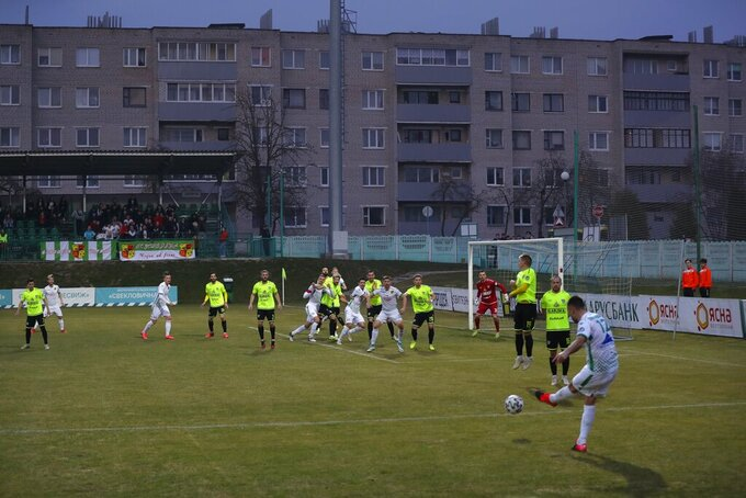 FILE In this photo taken on Saturday, March 28, 2020, Gorodeya's Milan Joksimovic, right back to camera, kicks the ball during the Belarus Championship soccer match between Gorodeya and Shakhter in the town of Gorodeya, Belarus. Longtime Belarus President Alexander Lukashenko refused to impose any restrictions, making Belarus the only country in Europe to continue playing professional soccer games with fans in the stands while the outbreak was in full swing. (AP Photo/Sergei Grits, File)