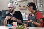 In this Oct. 7, 2020 photo, Andrew Rea, founder of the Binging with Babish network, left, tastes a beet parsnip licorice created by chef Sohla El-Waylly, during a taping of the