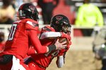 Texas Tech running back Xavier White (14) takes a handoff from quarterback Alan Bowman (10) during an NCAA college football game against Baylor in Lubbock, Texas, Saturday, Nov. 14, 2020. (AP Photo/Justin Rex)