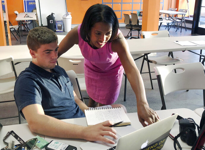 In this Wednesday, Aug. 29, 2018 photo, Jahana Hayes, right, Democratic nominee for Connecticut's 5th Congressional District, reviews photos in her Waterbury, Conn., campaign headquarters with campaign staffer Zeke Hodkin, who took a semester off from Middlebury College to be part of the candidate's social media team. Hayes, a former National Teacher of the Year, will face Republican Manny Santos in the November general election. (AP Photo/Susan Haigh)
