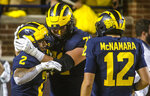 Michigan running back Blake Corum (2) celebrates his 67-yard touchdown with offensive lineman Andrew Stueber, center, and quarterback Cade McNamara (12) in the second quarter of an NCAA college football game against Washington in Ann Arbor, Mich., Saturday, Sept. 11, 2021. (AP Photo/Tony Ding)
