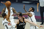 Brooklyn Nets' Kyrie Irving, right, knocks the ball loose from Cleveland Cavaliers' Cedi Osman, center, as Timothe Luwawu-Cabarrot tries to catch it during the first half of an NBA basketball game, Wednesday, Jan. 20, 2021, in Cleveland. (AP Photo/Tony Dejak)