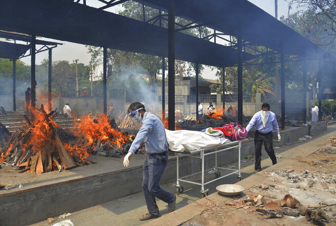 FILE - In this May 1, 2021, file photo, relatives carry the body of a person who died of COVID-19 as multiple pyres of other COVID-19 victims burn at a crematorium in New Delhi, India. COVID-19 infections and deaths are mounting with alarming speed in India with no end in sight to the crisis. People are dying because of shortages of bottled oxygen and hospital beds or because they couldn't get a COVID-19 test. (AP Photo/Amit Sharma, File)