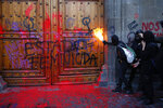 A masked, female protester sprays fire at the entrance to the National Palace, the presidential office and residence, after demonstrators covered it in fake blood and the Spanish message: