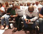 Family members of Hunter Brittain, sister Charli Brittain, from left, grandmother Rebecca Payne, and uncle Jesse Brittain, bow their heads for a prayer during the funeral service for 17-year-old Hunter Brittain, on Tuesday, July 6, 2021, at the Beebe Schools Auditorium in Beebe, Ark. Hunter Brittain was shot by a Lonoke County Sheriff's Deputy during a traffic stop on June 23. (Tommy Metthe/The Arkansas Democrat-Gazette via AP)