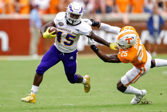 Tennessee Tech running back Jordan Brown (45) escapes from the grasp of Tennessee linebacker Morven Joseph (25) during the second half of an NCAA college football game Saturday, Sept. 18, 2021, in Knoxville, Tenn. Tennessee won 56-0. (AP Photo/Wade Payne)