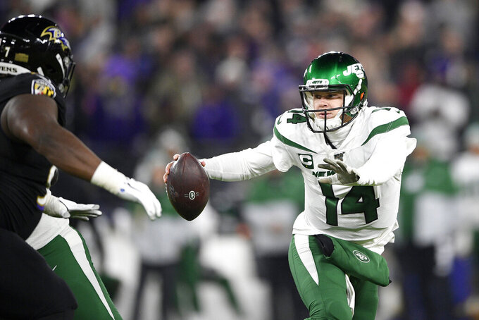 New York Jets quarterback Sam Darnold (14) tries to run away from Baltimore Ravens defensive tackle Michael Pierce, left, during the first half of an NFL football game, Thursday, Dec. 12, 2019, in Baltimore. (AP Photo/Nick Wass)