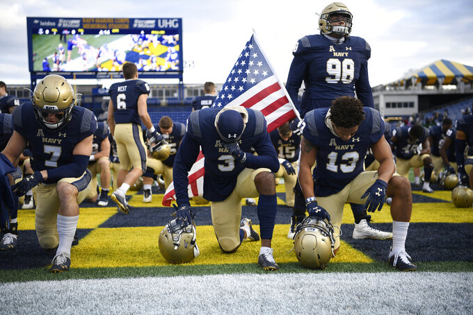 Navy cornerback Cameron Kinley (3), running back Chance Warren (13) and defensive lineman Mike Flowers (98) pause in the end zone before an NCAA college football game against Tulsa, Saturday, Dec. 5, 2020, in Annapolis, Md. (AP Photo/Nick Wass)