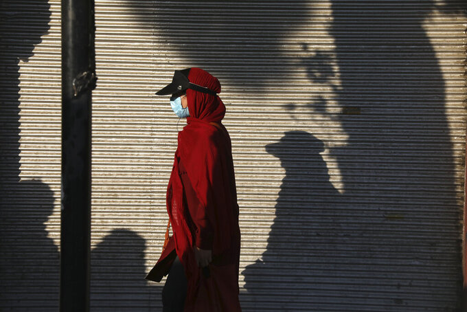 FILE - In this July 20, 2021 file photo, a woman wearing a protective face mask to help prevent the spread of the coronavirus walks on a sidewalk in southern Tehran, Iran. On Monday, Aug. 2, 2021, Iranian state media reported more than 37,000 new coronavirus infections, the country's single-day record so far in the pandemic. (AP Photo/Vahid Salemi)