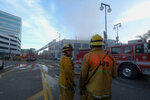 Los Angeles Fire Department firefighters work the scene of a structure fire that injured multiple firefighters, according to a fire department spokesman, Saturday, May 16, 2020, in Los Angeles. (AP Photo/Ringo H.W. Chiu)
