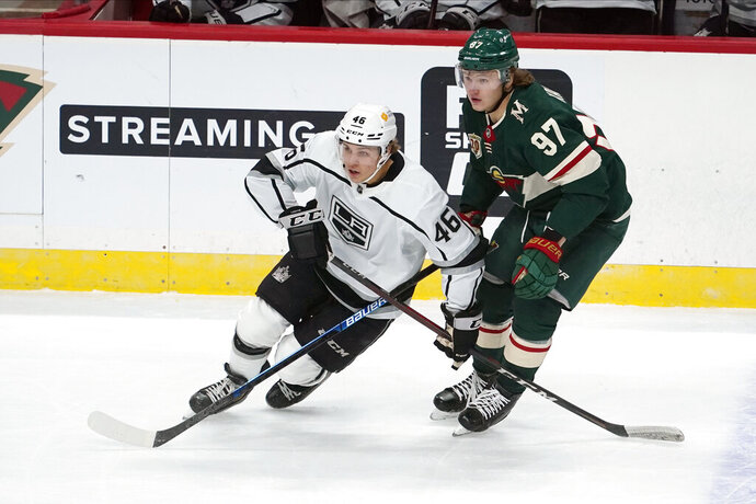 Los Angeles Kings' Blake Lizotte (46) and Minnesota Wild's Kirill Kaprizov (97) pursue the puck in the first period of an NHL hockey game, Tuesday, Jan. 26, 2021, in St. Paul, Minn. (AP Photo/Jim Mone)