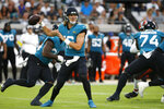 Jacksonville Jaguars quarterback Trevor Lawrence throws a pass during the first half of an NFL preseason football game against the Cleveland Browns, Saturday, Aug. 14, 2021, in Jacksonville, Fla. (AP Photo/Stephen B. Morton)