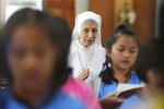 FILE -- In this Aug. 27, 2019 file photo, ST. Mary's School Vice Principal Sister Ana Rosa Sivori, center, and students pray inside a church at the girls' school in Udon Thani, about 570 kilometers (355 miles) northeast of Bangkok, Thailand. Sister Ana Rosa Sivori, originally from Buenos Aires in Argentina, shares a great-grandfather with Jorge Mario Bergoglio, who, six years ago, became Pope Francis. So, she and the pontiff are second cousins. In his visit to Thailand Pope Francis will be reunited with his second cousin, who has lived in Thailand since 1966 and will serve as Francis' official translator there. (AP Photo/Sakchai Lalit)