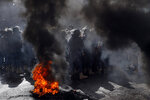 Riot police stand guard, as retired Lebanese soldiers burn tires during a protest in front of the government building, in Beirut, Lebanon, Monday, May 20, 2019. Lebanese security forces have opened heavy water cannons on anti-austerity protests in the capital city, as the government faces a looming fiscal crisis. Over one hundred protesters gathered Monday outside the Government House in downtown Beirut shouting