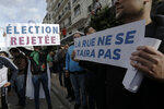 Algerian demonstrators take to the streets in the capital Algiers to reject the presidential elections, in Algeria, Thursday, Dec. 12, 2019. Five candidates have their eyes on becoming the next president of Algeria _ without a leader since April _ in Thursday's contentious election boycotted by a massive pro-democracy movement. Banner in French read